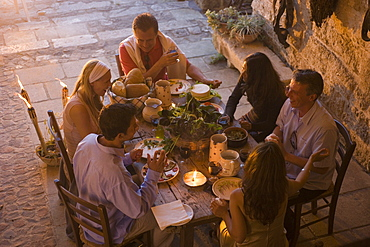 Group of people having dinner together on terrace, Apulia, Italy