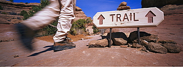 Hiker walking past a trail sign in the Grand Canyon, Utah, USA