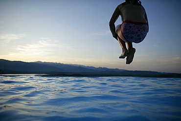 Girl jumping into pool, sunset, bay of Porto Vecchio, Southern Corse, France