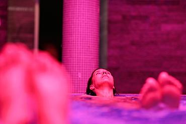 Woman lying in whirlpool, Hotel Krallerhof, Leogang, Salzburger Land, Austria