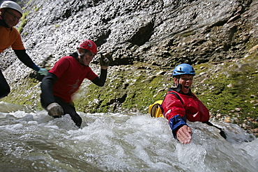 Men glinding through river, swim and hike canyon Raebloch, Emmental valley, Canton of Bern, Switzerland, MR