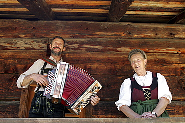 Mother and son sitting in front of log cabin, man playing Accordion, Salzburger Land, Austria