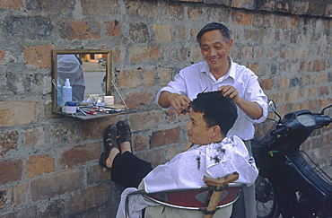 Hairdresser with client, open air, Hanoi, Vietnam