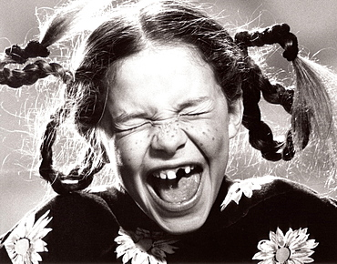 Screaming girl with missing front teeth, portrait