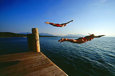 Man and women jumping in lake, Chieming, Chiemsee, Upper Bavaria