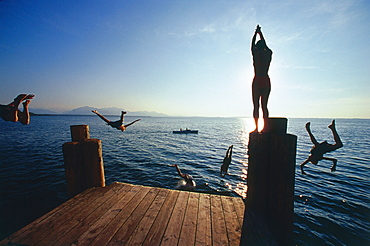 Teenager jumping from jetty in lake, Upper Bavaria, Germany, Chieming, Chiemsee, Upper Bavaria