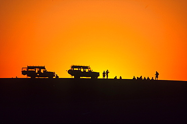 Jeeps and people at sunset, Walvis Bay, Namibia, Africa