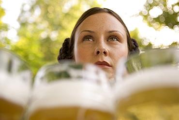 Waitress with beer steins in beer garden, Munich, Bavaria