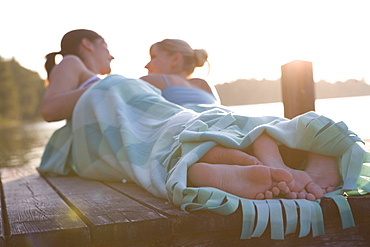 Two young women lying on boardwalk and looking at each other, Munich, Bavaria