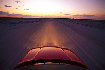 View at the bonnet of a BMW on a dirt road at sunset, Namibia, Africa