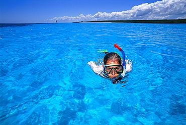 A woman snorkelling in blue water, Maternwe, Zanzibar, Tanzania, Africa