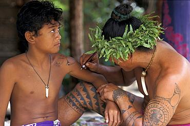A man wearing a headdress tatooing a boy at Tiki village, Moorea, French Polynesia, Oceania