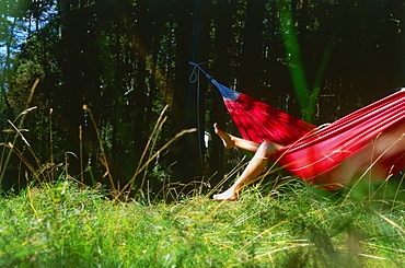 Young woman relaxing in hammock, legs hanging over side