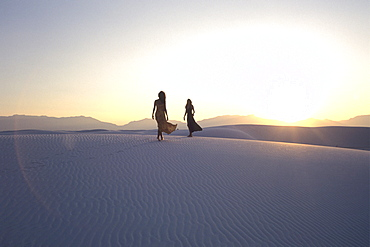 Women walking over dunes, White Sands National Monument, New Mexico, USA
