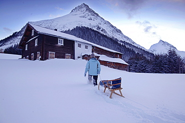 Woman with Sledge, Gorfenspitze and Ballunspitze in the background, Galtuer, Tyrol, Austria