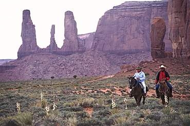 Two people on horseback near the Three Sisters, Monument Valley, Arizona, Utah, USA