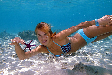 Woman diving, holding a starfish, Freediving, Under water, Mauritius