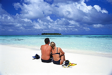 Young couple sitting on the beach, Hotel Banyan Tree Spa, Vabbinfaru, Maledives, Indian Ocean
