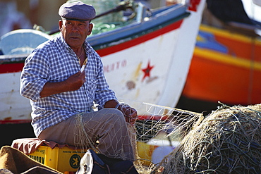Fisherman repairing a fishing net at harbour, Algarve, Portugal, Europe