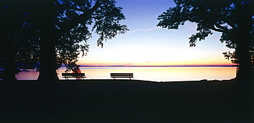 People sitting at the lakeshore, Rimsting, Chiemsee, Upper Bavaria, Germany