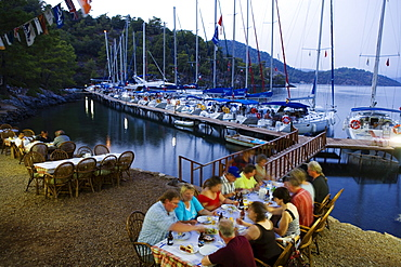People on the terrace of a restaurant at Sarsala Iskelesi bay, Fethiye, Turkey, Europe
