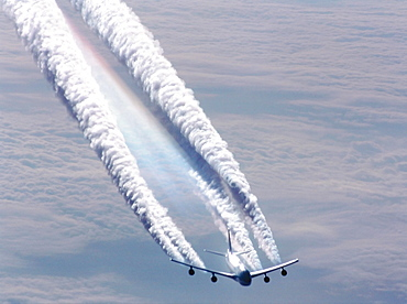 Plane flying over sea of clouds leaving huge condensation trails