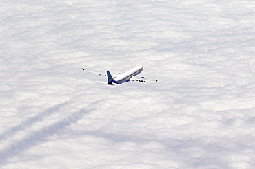 Airplane flying over sea of clouds