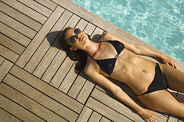 Young woman sunbathing at pool