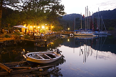 People on the terrace of a restaurant at a bay with jetty, Kapi Creek, Fethiye Bay, Turkey, Europe