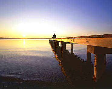 Man relaxing at end of wooden jetty, sunset, St. Heinrich, Upper Bavaria, Germany