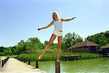 Bathing People, Young woman balancing on piles at jetty, Starnberger See, Bavaria, Dek