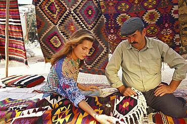 Tourist and salesman at a market stand with carpets, Bodrum, Turkey, Europe