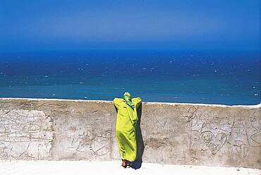 Woman leaning on a wall looking at the sea, Medina, Tanger, Morocco, Africa