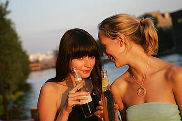 Two young women drinking beer, Berlin, Germany
