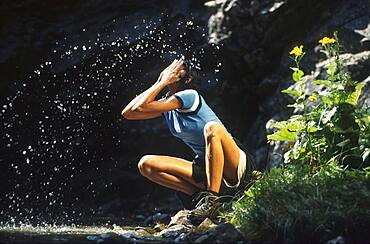 Young woman refreshing her face in a stream