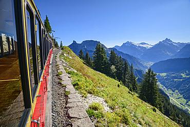 Red wagon of the rack railway travels to Schynige Platte, Bernese Alps in the background, from Schynigen Platte, Grindelwald, Bernese Oberland, UNESCO World Natural Heritage Swiss Alps Jungfrau-Aletsch, Bernese Alps, Bern, Switzerland