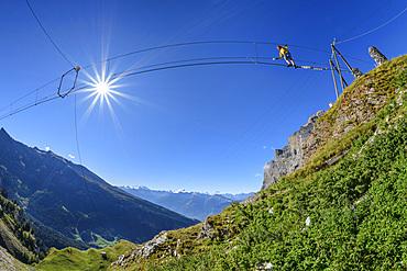 Woman on the Gemmi adventure via ferrata goes over rope bridge, Valais Alps in the background, Gemmi, Bernese Alps, Valais, Switzerland
