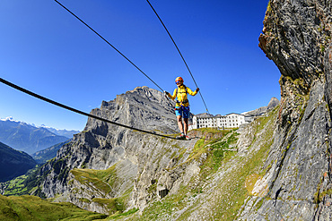 Woman on the Gemmi adventure via ferrata goes over rope bridge, Daubenhorn in the background, Gemmi, Bernese Alps, Valais, Switzerland
