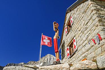 Hut Baltschiederklause with Swiss flag and wooden figure, Baltschiederklause, Bernese Alps, Valais, Switzerland