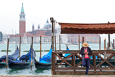 View of the Venetian gondolas and a gondolier on St. Mark's Square, in the background the island of San Giorgio, Venice, Veneto, Italy, Europe