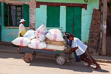 Malagasy people push cart, Madagascar, Africa