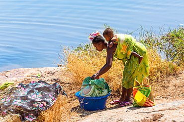Woman with baby washing clothes by the river, Southern Madagascar, Africa