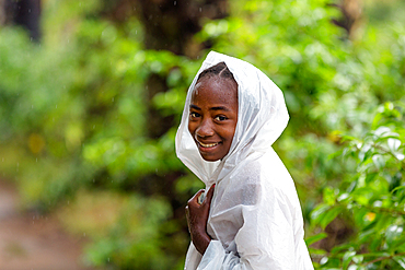 Young woman, girl with raincoat in the rain, southern Madagascar, Africa