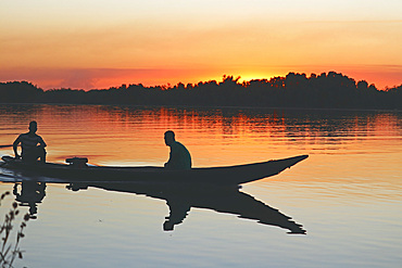 Gambia; Central River Region; Afterglow on the Gambia River near Kuntaur; two men sit in a boat near the shore