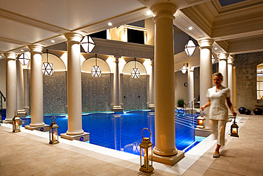 Evening shot of Spa therapist carrying lamps inside an intrioer pool room. Bath, United Kingdom