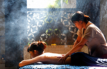 A Balinese therapist performing a massage on an Asian woman, in a smoky, romantic setting. Bali, Indonesia.