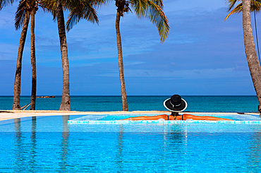 A woman in a black, white-rimmed hat, her back to the camera, rests on the side of a pool with an ocean view. Antigua, West Indies.