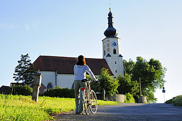 Woman pushing bicycle, Assumption of Mary pilgrimage church, Bad Koetzting, Bavarian Forest, Lower Bavaria, Bavaria, Germany