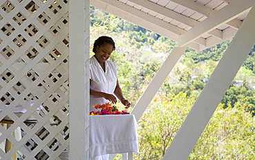 Spa therapist preparing flowers in a white cabana. St. Lucia, West Indies.
