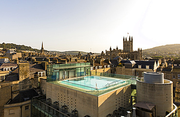 View of exterior roof-top pool set against the scenery of old turrets and buildgs, Horizontal. Bath. United Kingdom